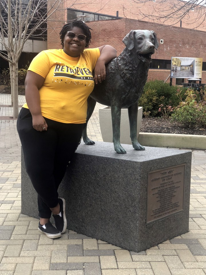 "Women in gold ""Retrievers"" shirt, black pants, and sunglasses stands next to statue of of a retriever dog."