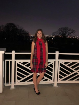 White woman in dress and scarf stands outdoors in the evening, next to a white fence.