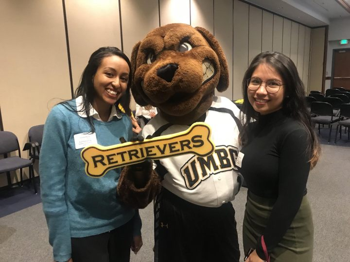 Two students flank a dog mascot