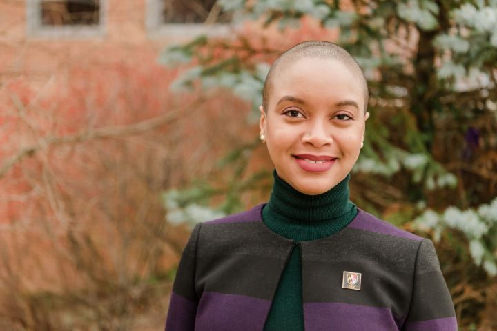 "Portrait of a black woman in a striped blazer and turtleneck shirt, wearing pin that reads ""UMBC."""