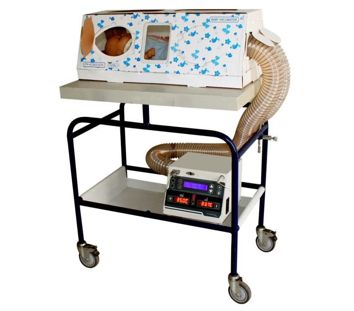 A black and white rectangular push cart with two levels carries a card board box with small blue flowers on the front of the box. Inside the box is a baby doll. A plastic ribbed tube is inserted into the end of the box that connects to a digital medical monitor box beneath.