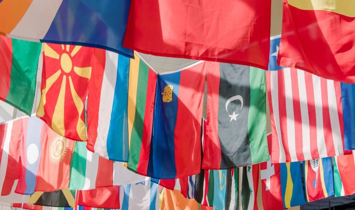 Flags from nations around the world hanging in the air, brightly lit by natural light from a window