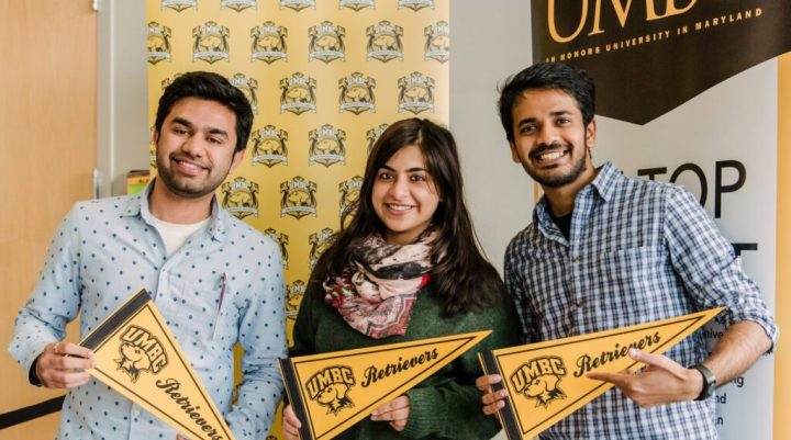 Three young adults smile at camera, holding pennants that read UMBC Retrievers