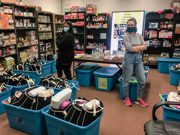 Two young women wearing blue face masks stand facing away from each other while smiling at the camera in a room lined with shelves filled with cans of food. On the floor around them are large blue tubs with black and white bags filled with a variety of objects.