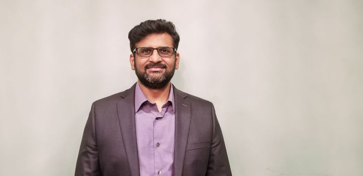 Portrait of a middle-aged South Asian man. He has a beard and wavy hair, and wears wire-framed glasses and a suit.