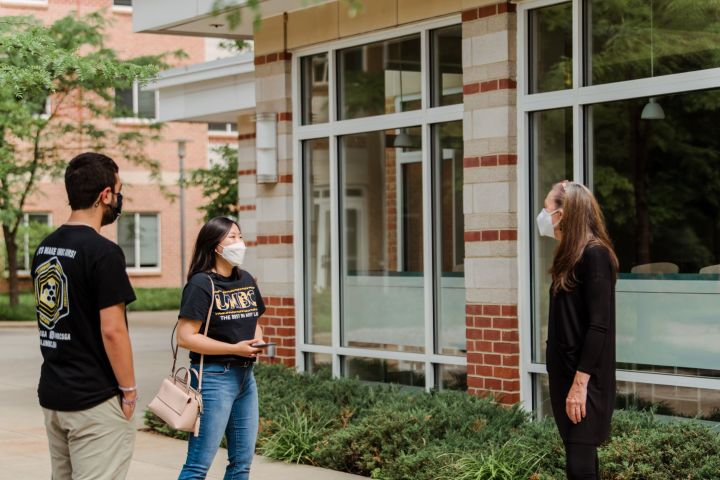 "Three people stand outside a building, all wearing masks. Two wear black and gold t-shirts, with one reading ""UMBC."""
