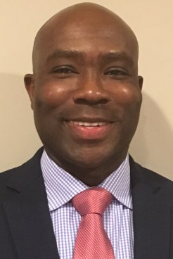 Portrait of smiling middle-aged Black man in suit, striped shirt, and pink tie.