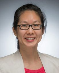 Headshot of woman wearing glasses, cream blazer and pink shirt