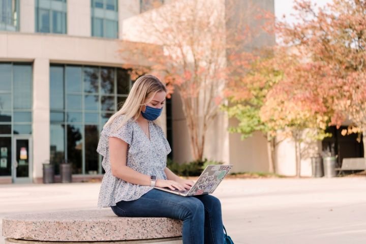 Young white woman with blonde hair sits in front of a building, typing on a laptop. She wears jeans and a flowy patterned shirt.
