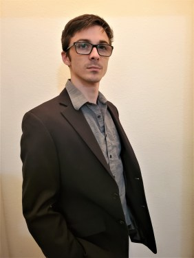 A young man with short brown hair wearing dark rimmed glasses and a brown dress shirt and jacket stands in front of a beige wall and looks into the distance.