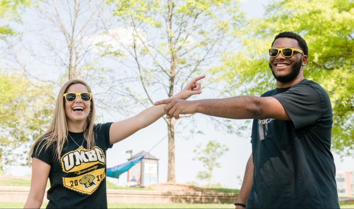 Two college students (a white woman and Black man) smile for an outdoor portrait. They point toward each other. They wear sunglasses and black and gold UMBC t-shirts.