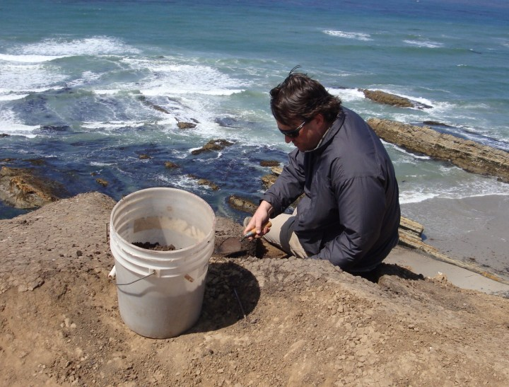 A man wearing a blue jacket sits on a cliff by the sea with shoveling  small mounds of dirt into a white bucket.