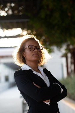 Outdoor portrait of a young black woman wearing a suit and glasses. The sunlight shines behind her.