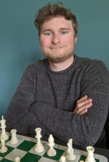 Portrait of a smiling young man in a gray sweater. He sits behind a chess board.
