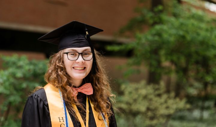 Young adult with long, curly hair smiles for a portrait, wearing graduation regalia and a bow tie.