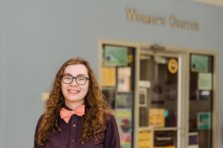 """Young adult with long, curly hair smiles for a portrait, wearing a dress shirt and bow tie. The sign behind them reads """"Women's Center."""""""