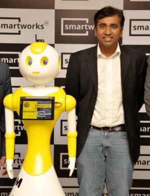 A man wearing a white shirt, dark jacket, and jeans, stands next to a yellow and white robot. There is a screen on the middle of the robot.