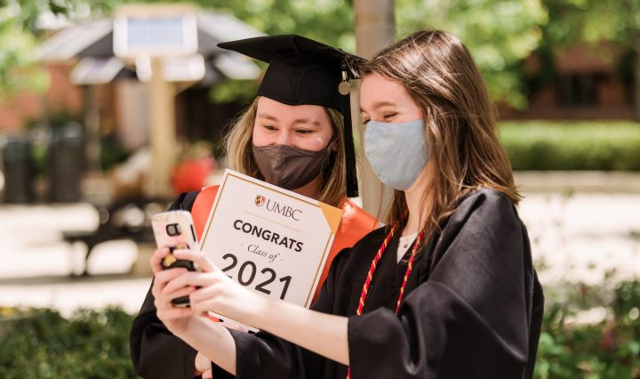 """Two students, both wearing masks and graduation regalia, take a selfie. One student is holding a """"Congrats Class of 2021"""" sign."""
