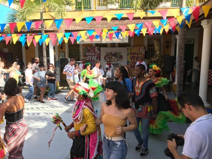 A group of people wearing brightly colored clothes dance in a circle in an outdoor plaza.