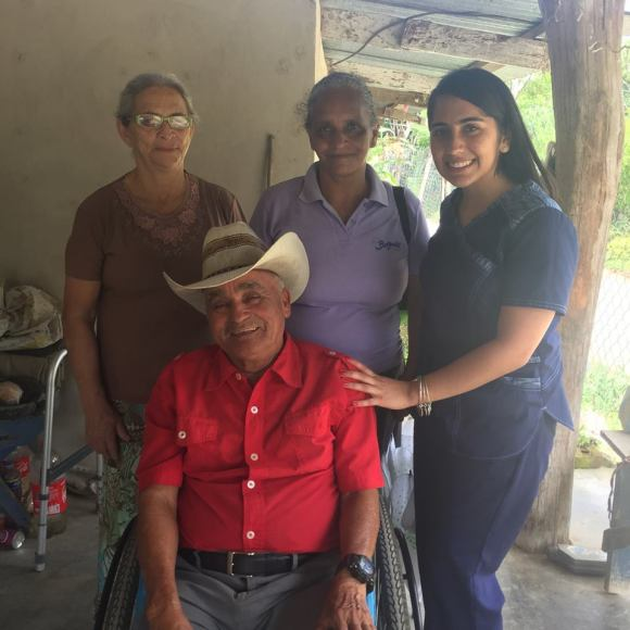Student in healthcare scrubs with three older Hondurans