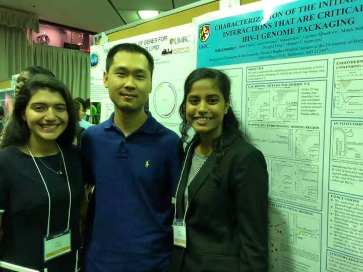 Three researchers in a busy poster hall