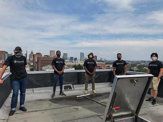 Five young men wearing black t-shirts and face masks stand on the roof of a building with a city landscape behind them.
