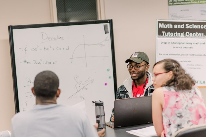 """A young black man in glasses and a baseball cap reading """"CODE"""" sits  with two other people, speaking together. Math problems are on a whiteboard in the background."""