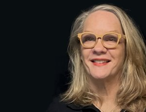 A white woman with light brown glasses.