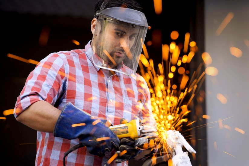 Joshua Ramirez, advocate and Trojan, photographed outside working in the USC Roski sculpture yard. He is using a power tool, wearing a face shield, and sparks are flying from his tool as he is working on a rock.