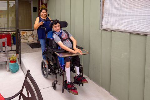 Transfer student Margarita Lopez wheeling her son down a ramp in his wheel chair.