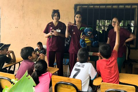 Nikki Aflatooni a volunteer at Global Dental Brigades teaching children to brush their teeth, through support of their scholarship.