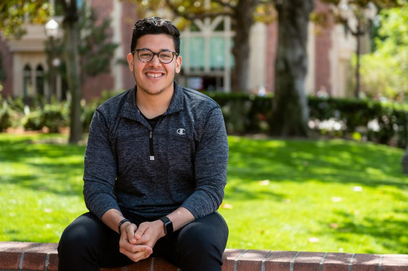 USC graduate  Mounir Ghabrial, who is passionate about entrepreneurship, photographed on USC campus, sitting on a bench, and looking into the camera and smiling.