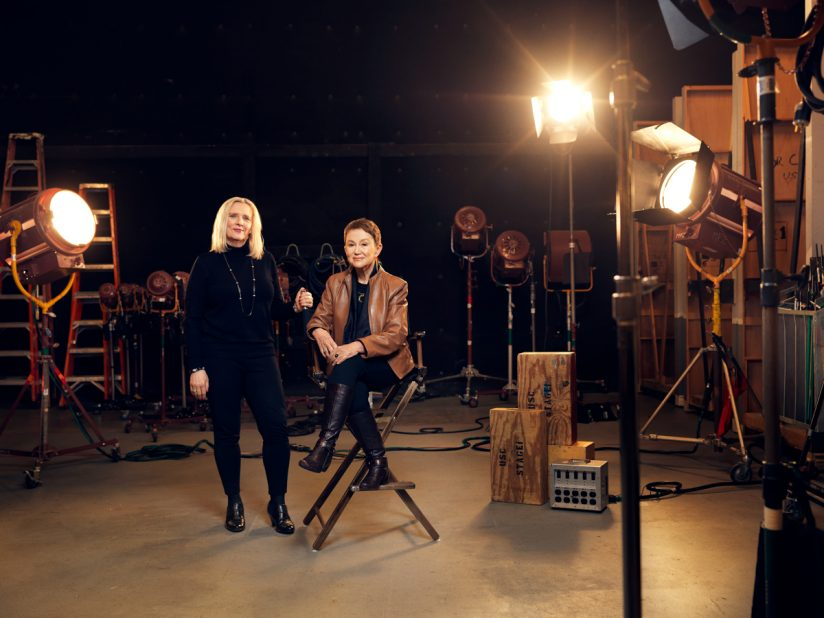 Elizabeth Daley and Marlene Loadvine of the USC School of Cinematic Arts, photographed together on a sound stage, with Marlene sitting next to Elizabeth in a chair, and both are surrounded by spotlights.