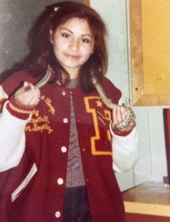 Ana Gonzales is wearing her red and white high school letterman jacket. She is holding a snake around her neck.