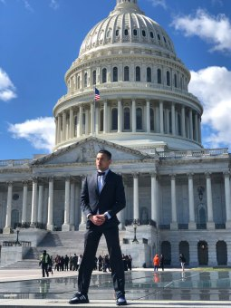 Latinx advocate Xavier Hernandez is photographed in standing outside of the DC capitol building wearing a business suit.