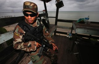 A Malaysian sailor stands guard on the beach near Lahad Datu. Reuters Photo
