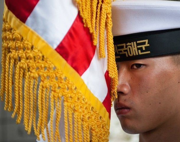 Republic of Korea Navy sailor holding U.S. flag