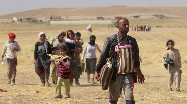 Displaced people from the minority Yazidi sect walk toward the Syrian border on the outskirts of Sinjar mountain on Aug. 11. Reuters Photo