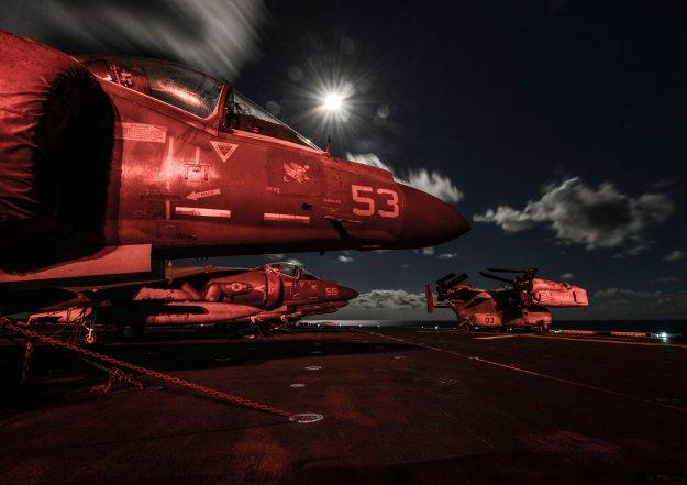 AV-8B Harriers sit on the flight deck at night aboard the amphibious assault ship USS Bataan (LHD-5) on Oct. 3, 2014. US Navy Photo