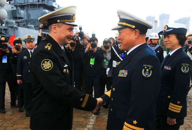 Rear Adm. Du Xiping (front right), deputy commander of China's Beihai Fleet, shakes hands with Capt. 1st Rank Sergei Yuriyevich Zhuga of Russia's Pacific Fleet during a welcome ceremony at a naval base in Qingdao, in east China's Shandong Province, on April 21, 2012. Xinhua Photo