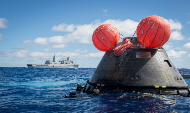 Navy divers assigned to Explosive Ordnance Disposal Mobile Unit (EODMU) 11 and Mobile Diving and Salvage Company 11‐7, attach a towing bridle to the NASA Orion crew module on Dec. 5, 2014. US Navy Photo