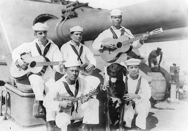 Filipino Stewards and their mascot on USS Seattle during WWII. Dogs were popular mascots in all the U.S. sea services.