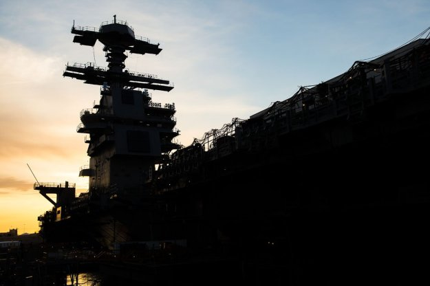 Aircraft carrier Gerald R. Ford (CVN-78) sits pier side in the early morning light at Newport News Shipbuilding in 2014. US Navy Photo