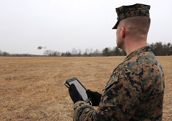 A Marine uses a handheld tablet to request resupply during an Office of Naval Research (ONR) helicopter flight demonstration with unmanned flight capability at Marine Corps Base Quantico, Va., as part of the Autonomous Aerial Cargo Utility System (AACUS) program in early 2014. US Navy Photo