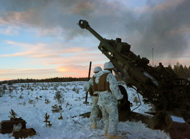 Marines with Combined Arms Company, step back as an M777 Howitzer fires a round during a live-fire shoot in Rena, Norway, Feb. 23, 2016. U.S. Marine Corps Photo