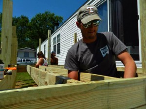 Student Brice Holmes constructs the deck of Barbara Beilke's home.