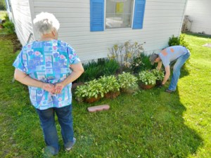 Brice Holmes helps with planting as resident Barbara Beilke looks on.
