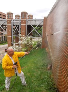 UT Facilities Services employee Bill Mills cleans graffiti from a university building.