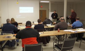 """Klaus Blache, director of UT's Reliability and Maintainability Center, talks to students during the """"Spare Parts and Best Practices—A Practical Approach"""" class in the spare parts lab in January."""