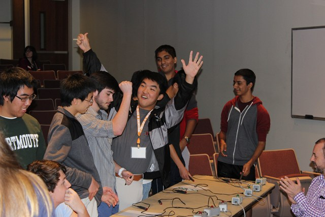 Houston High School's Brandon Hong raises his hands in the air in celebration after his team won he Engineers Day quiz bowl.